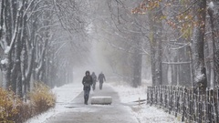 Winter snowfall, people walking along alley, beautiful snowy day in the city Stock Footage