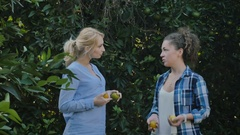 Two funny young women show oranges as their breast and dancing with it near tree Stock Footage