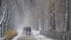 People walking along slippery sidewalk, first snowfall, risk of accidents Stock Footage