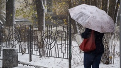 Woman with umbrella waiting for someone, snowfall, first winter day Stock Footage