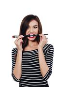 Cute beautiful girl artist Brush teeth bit into the paint in the process draws Stock Photos