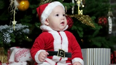 Cute boy playing near the Christmas tree, Little baby dressed in Santa outfits Stock Footage