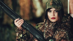 Girl in a military uniform and with a pump-action shotgun. posing on camera Stock Footage