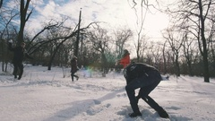 Group of friends playing snowballs and having fun in snowy park, slow motion Stock Footage