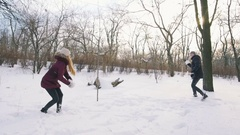 Young couple playing snowballs and having fun in snowy park, slow motion Stock Footage