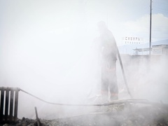 Fire Hose Extinguishes. Fireman Standing in the Smoke. View of the Burned Stock Footage