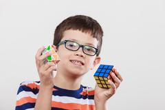Smart kid little boy with magic rubik cube. Stock Photos