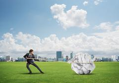 Man pulling with effort big crumpled ball of paper as creativity sign Stock Photos