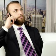 Handsome business man with beard working in office on laptop and cell phone Stock Photos