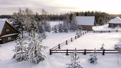 Sunset in the countryside in the winter season. Snow-covered courtyards of house Stock Footage