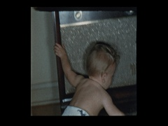 Baby boy in diapers plays with antique television set Stock Footage