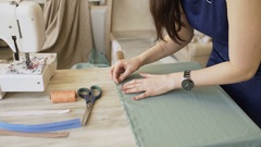 Young clothing designer and seamstress woman sew with thread and needle near Stock Footage