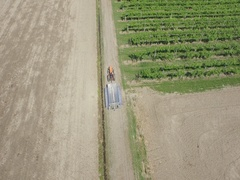Drone on the Tuscan vineyards with a tractor working Stock Footage