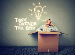 Think outside box. Woman coming out of box with great idea Stock Photos