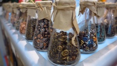 Glass jars with different rivets for jeans standing in a row at the show Stock Footage