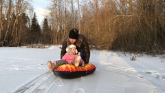Dad pushes her daughter on a rubber inflatable snow tube Stock Footage