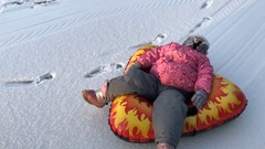 Little girl and rubber inflatable snow tube Stock Footage