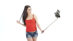 Long-haired brunette makes selfie using a monopod. Studio. White background Stock Footage