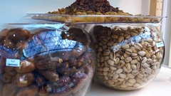 Pistachios, dates and raisins in glass jars on showcase Stock Footage