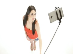 Brunette girl doing selfie photos using a monopod. White background Stock Footage