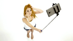 Redheaded girl doing selfie photos using a smartphone and monopod Stock Footage