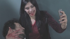 Funny female vampire taking selfie with cell phone holding dead man Stock Footage