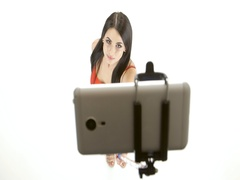 Brunette girl doing selfie photos using a smartphone and monopod Stock Footage