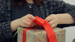 Brown-haired designer ties bow on packing new year present isolated Stock Footage