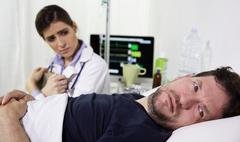 Man in hospital bed, scared after receiving the diagnostic test results. He.. Stock Photos