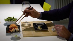 Slow motion video of  man with a beard eating sushi and drinking white .. Stock Footage