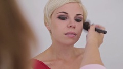 Professional make-up artist applying powder to woman s face Stock Footage