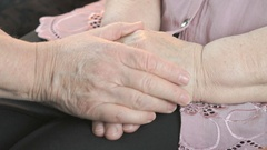 Woman strokes old woman's hands during illness Stock Footage
