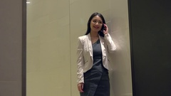 Attractive Asian Woman Talking On Mobile Telephone In Office Building Stock Footage