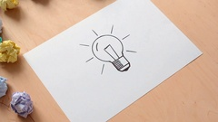 Hand is whisking away crumpled papers from drawn light bulb Stock Footage
