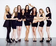 Many diverse women in line, wearing fancy little black dresses Stock Photos