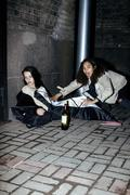Young poor ttenage girl sitting at dirty wall on floor with bottle of vine, poor Stock Photos