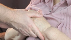 Man strokes old woman's hands in times of stress Stock Footage