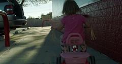 Toddler Girl Riding Trike on Sidewalk Stock Footage