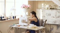 Young clothing designer and seamstress woman work with sewing machine in tailor Stock Footage
