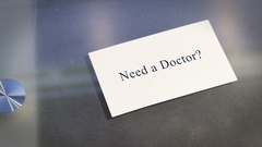 Hand puts business card on table with text Need a Doctor Stock Footage