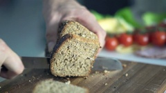 Close up of female hands slicing whole grain bread, super slow motion 240fps Stock Footage