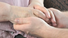 Man soothes elderly woman during stress Stock Footage