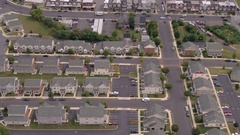 AERIAL: Identical perfect row houses in stunning suburban town near busy highway Stock Footage