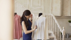 Young clothing designer and seamstress sew shirt with thread and needle in Stock Footage