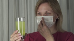 Woman drinking effervescent antipyretics pill dissolved in glass of water Stock Footage