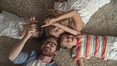 Top view of parents and their little kids lying on the floor at home and playing Stock Footage