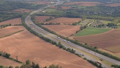 AERIAL: National interstate highway running through farmlands, fields and forest Stock Footage