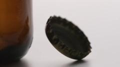 SLOW MOTION: Bottle cap falls near a brown bottle - macro shot Stock Footage