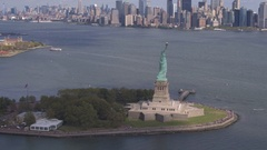 AERIAL: Flying around Statue of Liberty in front of downtown New York city Stock Footage