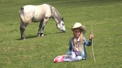 4K Farmer Cowboy Child Pasturing Horses, Smiling Girl Playing Outdoor on Meadow Stock Footage
